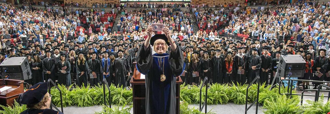 Chancellor Henry taking selfie on stage during Commencement
